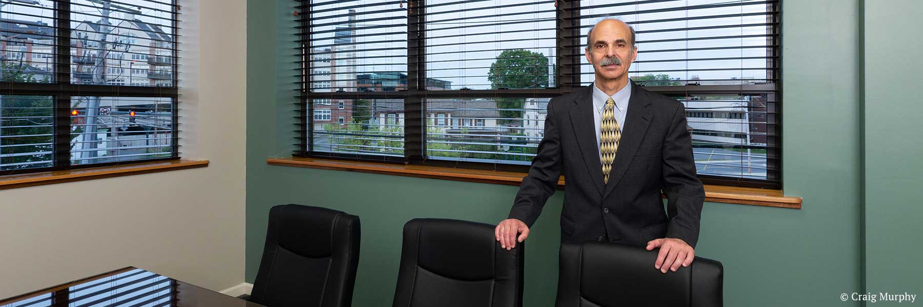 New York State lawyer Neil H. Lebowitz posing in conference room with Glens Falls, New York cityscape view in background. Photographer: Craig Murphy. Copyright owner-licensor: Craig Murphy. Copyright licensee: Neil H. Lebowitz.